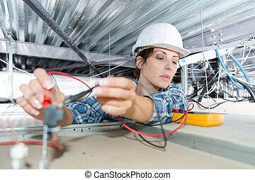 femme, électricien, vérification, tension, de, plafond, câbles