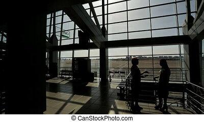 femme, aéroport, deux, silhouettes, couloir départ, parler