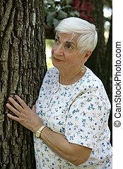 femme aînée, à côté de, arbre