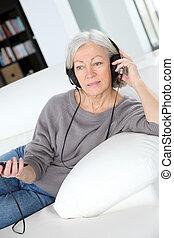 femme aînée, écouter musique, à, écouteurs