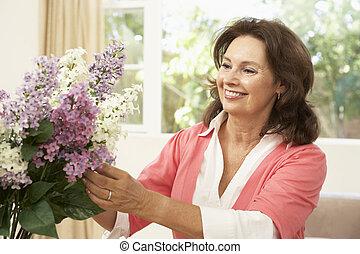 femme aînée, chez soi, arrangement fleurs