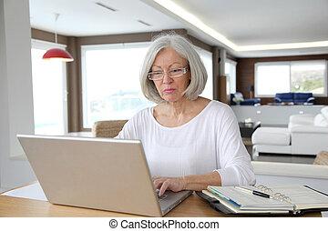 devant t l phone ordinateur portable personne g e femme. Black Bedroom Furniture Sets. Home Design Ideas