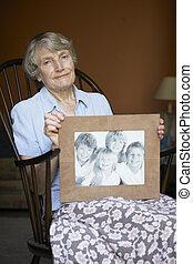femme aînée, chez soi, regarder, photo, de, petits-enfants