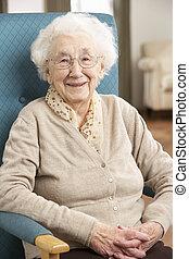 femme aînée, délassant, dans chaise, chez soi