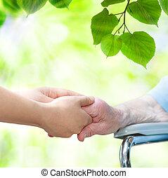 femme aînée, dans, chaise roue, tenant mains, à, jeune, gardien