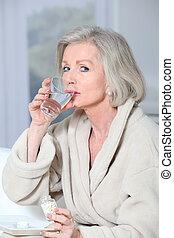 femme aînée, dans, peignoir, prenant pilules