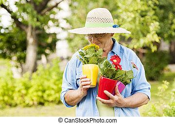 femme aînée, fleurs, sentir