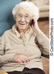 femme aînée, parler téléphone portable, reposer dans chaise, chez soi