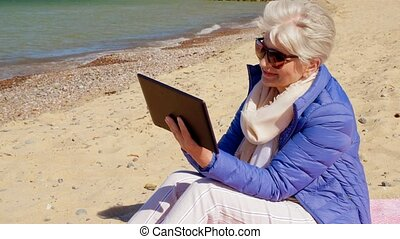 femme aînée, plage, tablette, informatique