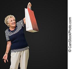 femme aînée, regarder, sacs provisions