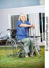 femme aînée, séance, sur, fauteuil roulant, à, clinique, pelouse