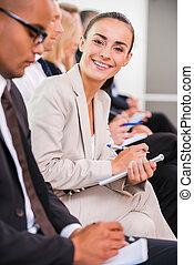 femme affaires, à, les, conference., vue côté, de, professionnels, séance, rang, et, écriture, quelque chose, dans, leur, note, coussins, quoique, confiant, jeune femme, regarder appareil-photo, et, sourire