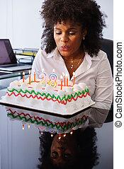 femme affaires, célébrer, fêtede l'anniversaire, dans, bureau, souffler, bougies