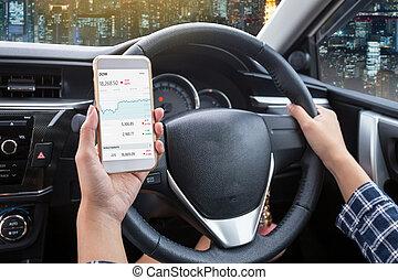 femme affaires, chauffeur, a, écran tactile, de, blanc, smartphone, chèque, bourse, ou, échange, et, possession main, volant, dans voiture, à, nuit, ville, fond