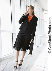 femme affaires, marche, dans, couloir, parler téléphone cellulaire