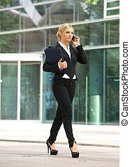 femme affaires, marcher parler, sur, cellphone, dans ville