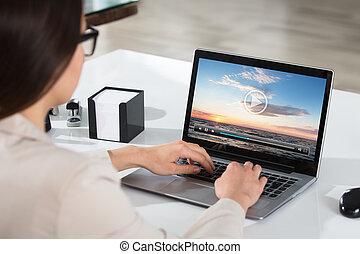 femme affaires, ordinateur portable, vidéo, regarder