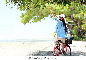 femme, amusant, bicyclette voyageant, plage