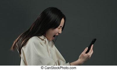 femme asiatique, bas, utilisation, somebody., téléphone, mobile, fâché, crier, swears