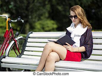 femme, asseoir, sur, banc, et, lire, livre