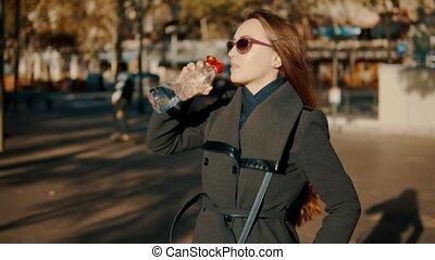 femme, assoiffé, business, ouverture, bouteille eau, dehors, boire