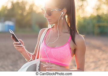 femme, athlète, smartphone, écoute, musique, regarder