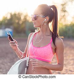 femme, athlète, smartphone, écoute, séance entraînement, musique, regarder