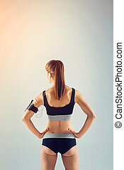 femme, athlète, tourné, dos, musique écouter, vêtements de sport