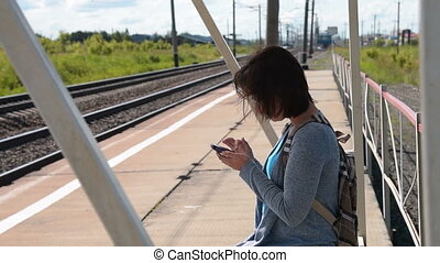 femme, banlieusard, quand, cellule, plate-forme, attente, train, utilisation