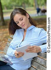 femme, bloc-notes, garez banc, tenue, assis