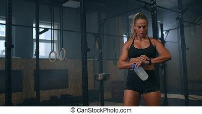 femme, bouteille, sports, après, chèques, contrôler, séance entraînement, pouls, coeur, athlétique, watch., eau, taux, gymnase