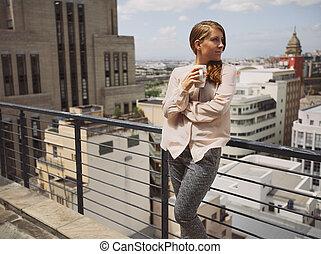 femme, café buvant, et, apprécier, vue ville, depuis, balcon