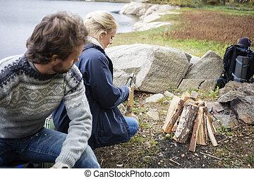 femme, camping, regarder, bois, couper, homme