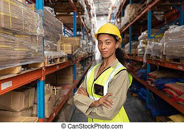 femme debout, armes traversés, ouvrier, entrepôt