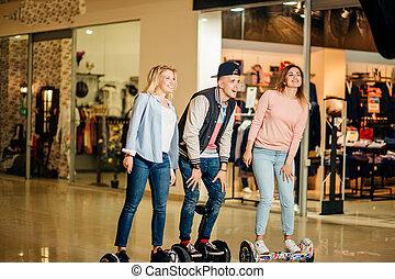 femme, deux, centre commercial, équitation, hoverboard, homme
