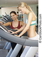 femme, fonctionnement, à, femme, entraîneur personnel, sur, machine courante, dans, gymnase