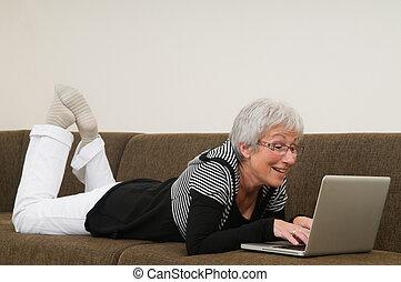 femme, fonctionnement, séance, décontracté, ordinateur portable, couch., personne agee