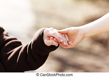 femme, gardien, jeune, tenant mains, personne agee