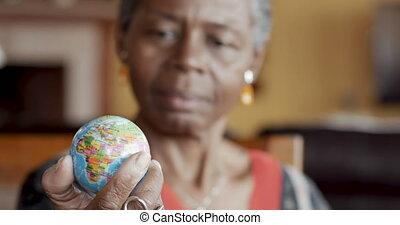 femme, globe, foyer, regarder, américain, séduisant, africaine, mondiale, personne agee, étagère