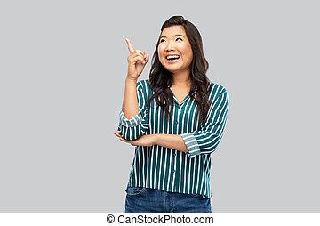 femme, gris, asiatique, heureux, doigt, haut, pointage