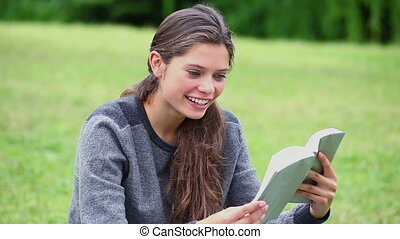 femme heureuse, brunette, livre, lecture