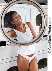 femme heureuse, regarder travers, machine à laver, porte