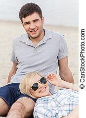 femme heureuse, séance, plage, couple, jeune, homme, séduisant, jambes, summer., mensonge, lunettes
