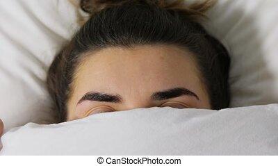 femme, heureux, lit, couverture, jeter coup oeil, sous
