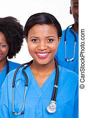 femme, infirmière, à, collègues, arriere-plan