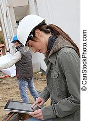 femme, ingénieur, à, blanc, sécurité, casque, debout, sur, site construction