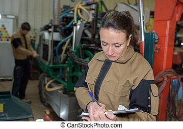 femme, ingénieur, à, presse-papiers, dans, usine