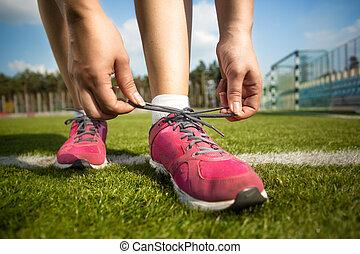 femme, jeune, chaussure de course, attachement, avant, dentelles
