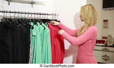 femme, jeune, choisir, salle exposition, étagère, vêtements