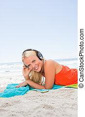 femme, jeune, quoique, musique écouter, sourire, plage, blond, mensonge